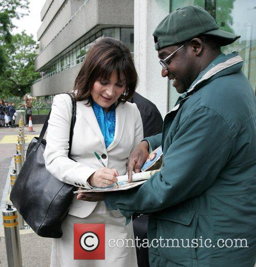 Lorraine Kelly signs an autograph for a waiting...