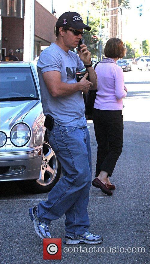 Mark Wahlberg carries brand new golf balls outside...