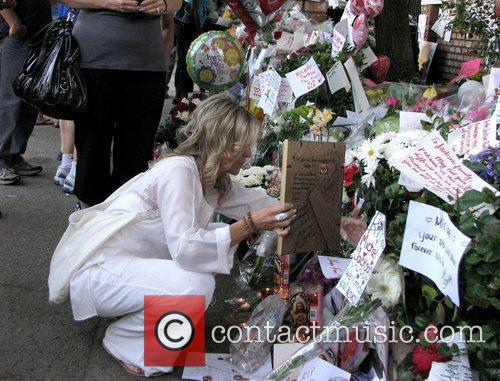 Fans lay hundreds of flowers, banners and other...