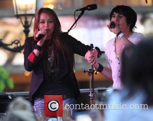 Miley Cyrus and Mitchel Musso perform at a...