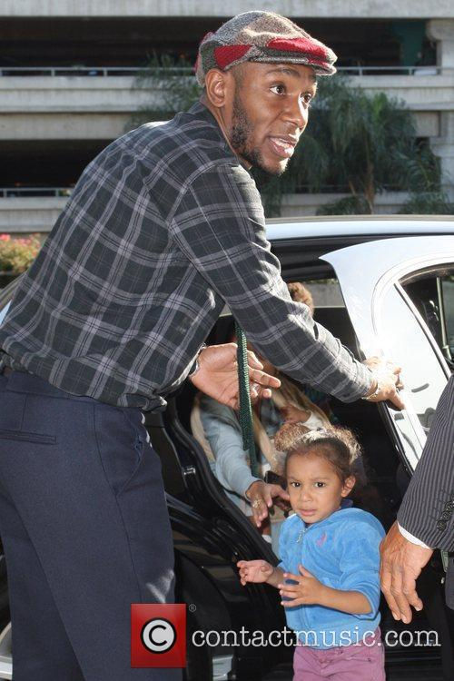 Mos Def getting into a limousine with his...