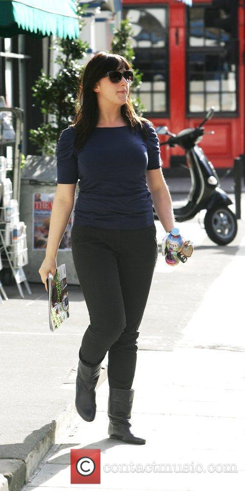Natalie Cassidy  out and about holding a...
