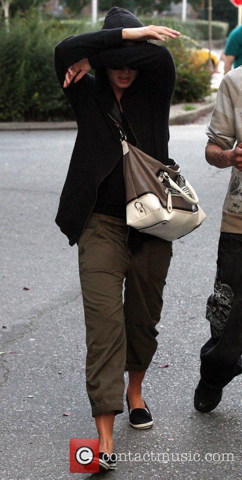 Nikki Reed tries to hide her face from...