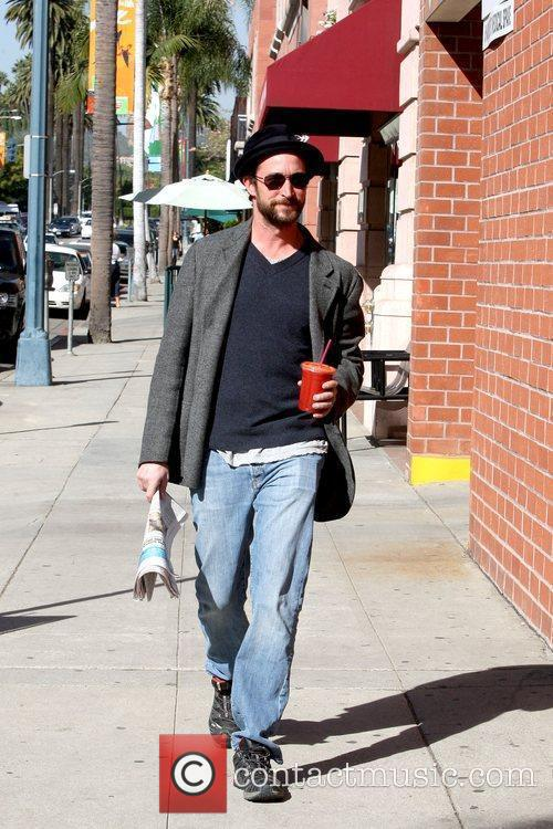 Noah Wyle holding a cold beverage and newspaper...