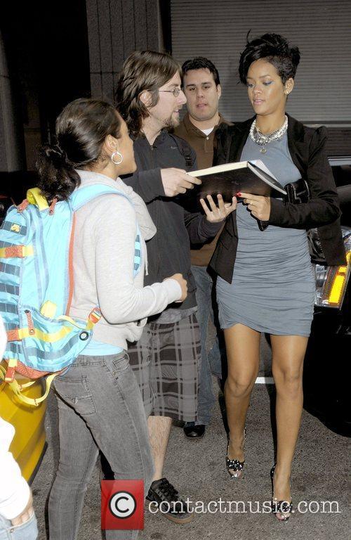 Rihanna outside her Manhattan hotel signing an autograph...