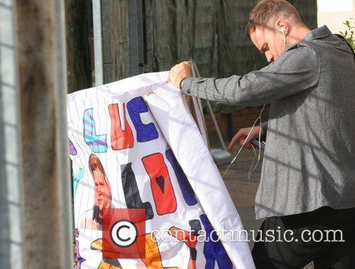 Olly Murs holding a good luck banner outside...