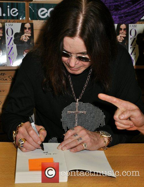 Signing copies of his book 'I Am Ozzy'...