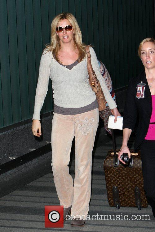 Penny Lancaster pulling her Louis Vuitton luggage as...