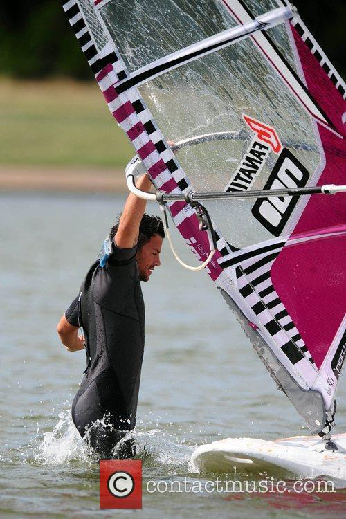 Peter Andre climbs back onto his board during...