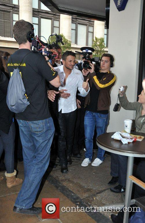 Peter Andre is mobbed by the paparazzi outside...