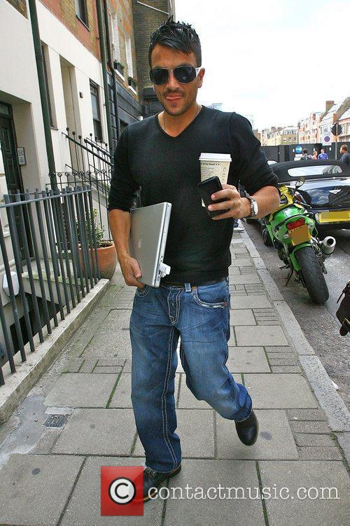 Peter Andre arriving at a meeting carrying a...