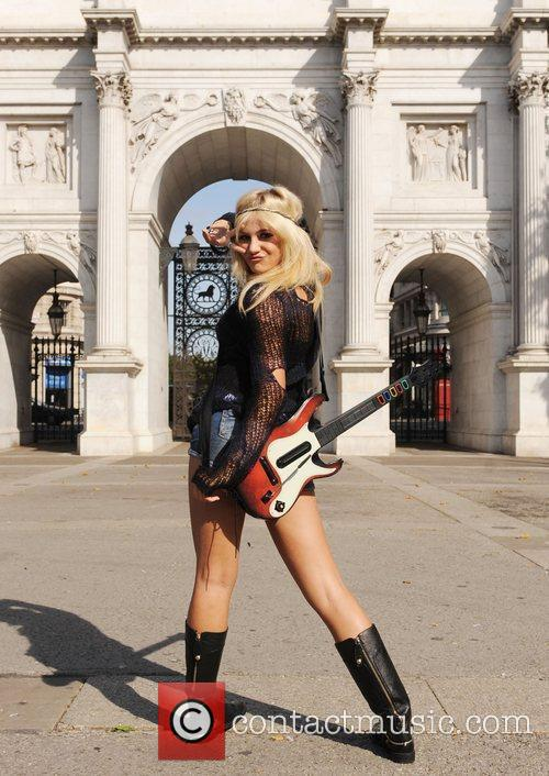 Promotes Guitar Hero 5, posing in front of...