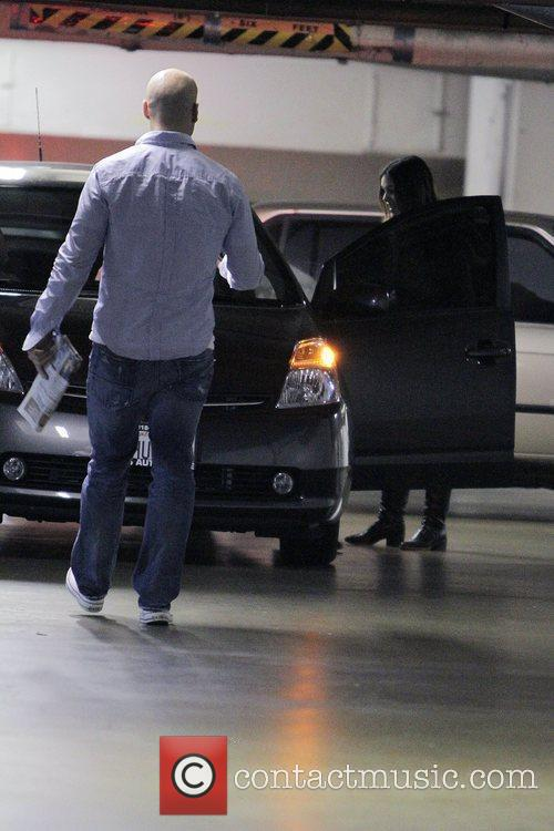 Rachel Bilson drives out of a parking garage...