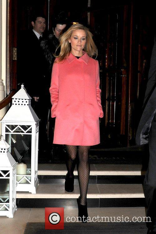 Departs her hotel wearing a bright pink coat