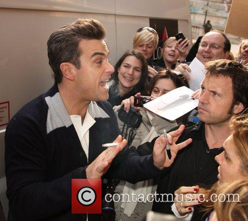 Robbie Williams signs autographs for fans while smoking...