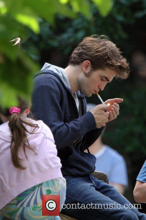 Robert Pattinson lights a cigarette on the set...