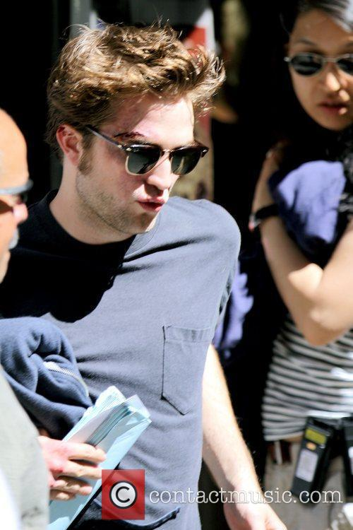 Robert Pattinson holding a script while on the...