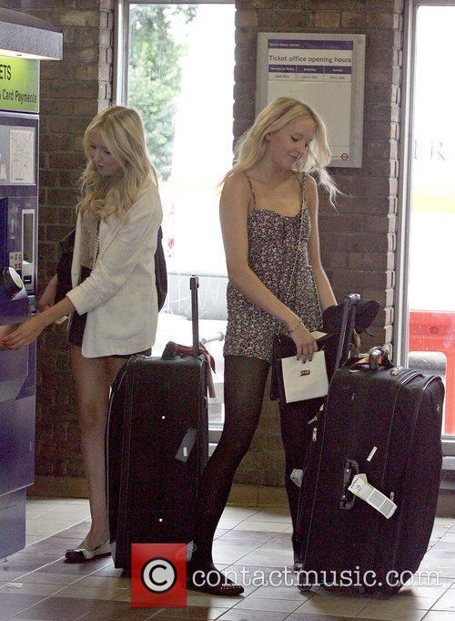 Standing with luggage as they purchase tickets at...