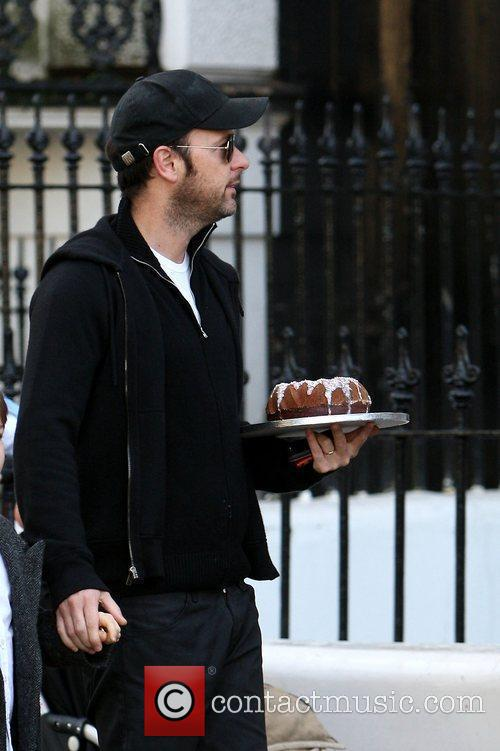 Carrying a cake as he takes his son...