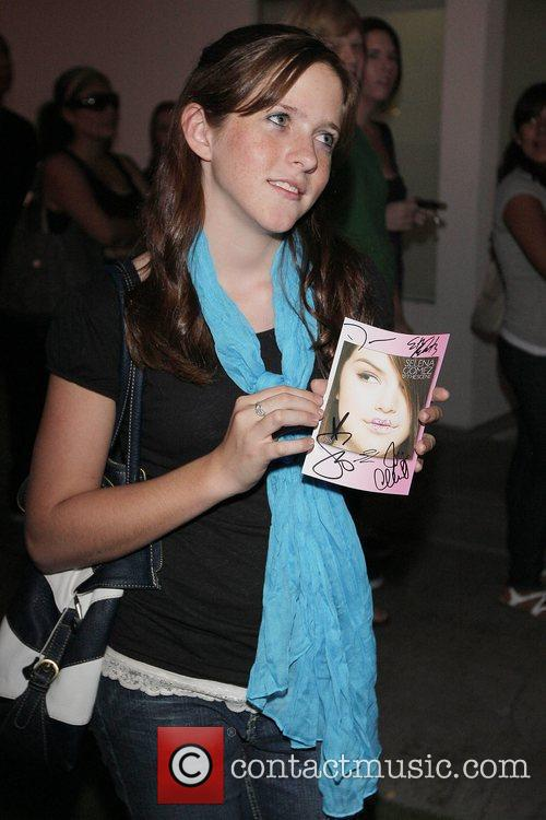 A fan holding an autograph of Selena Selena...