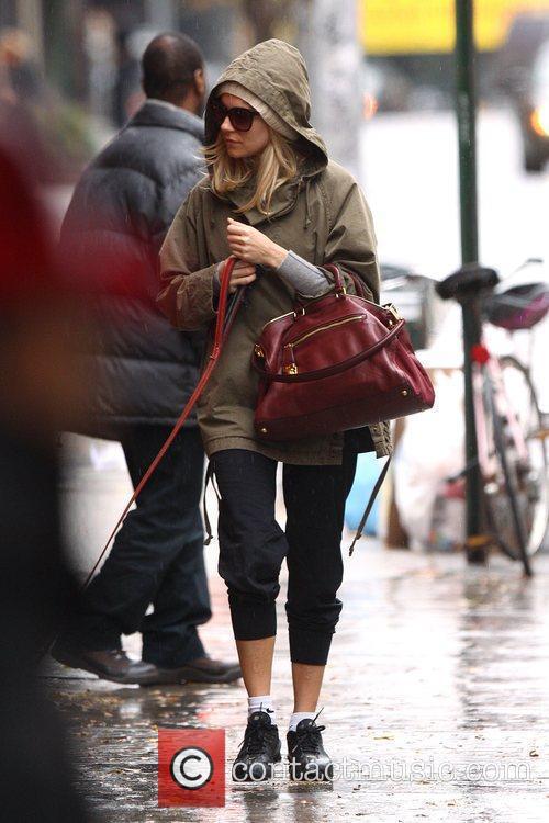 Sienna Miller braves the early morning rain to...