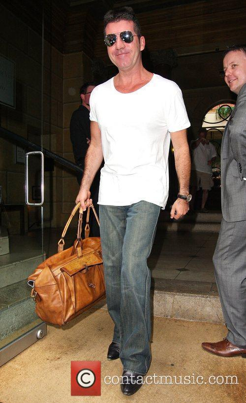 Simon Cowell smiling as he leaves his hotel...