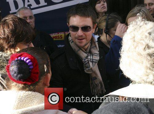 Craig Kelly is crowded by fans as he...