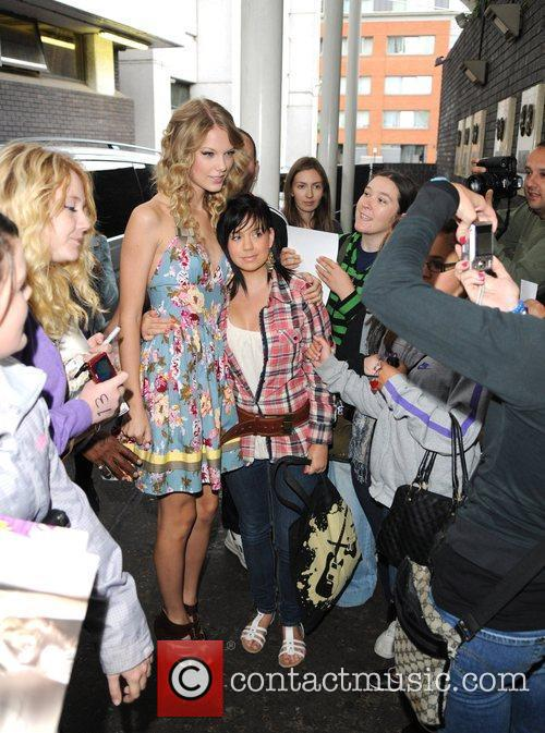 Taylor Swift poses for photos with fans as...