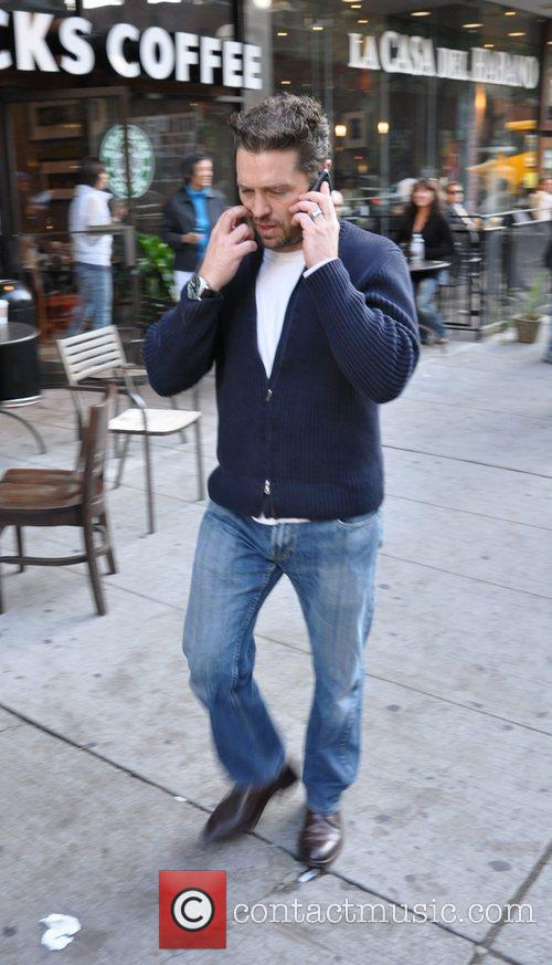 Chats on his cellphone as he takes a...