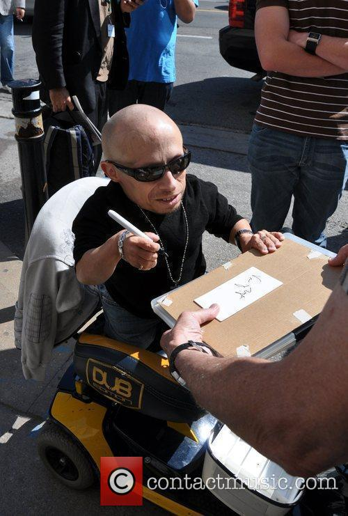 Verne Troyer signs autographs for fans while sitting...