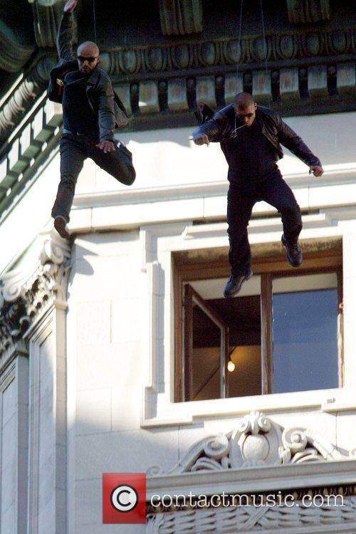 Stuntmen suspended on wires, jump off a building...