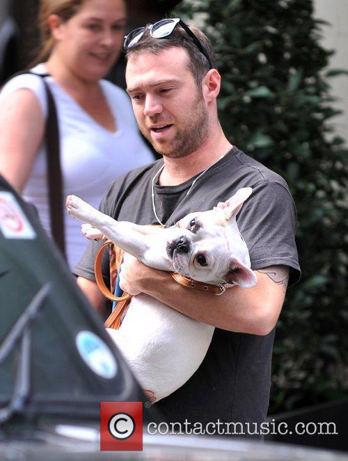 Leaves his hotel with girlfriend Sarah Harding's dog...