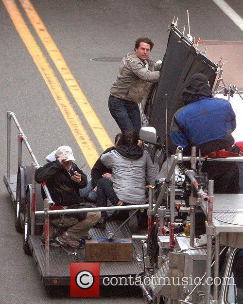 Tom Cruise filming a stunt scene on top...