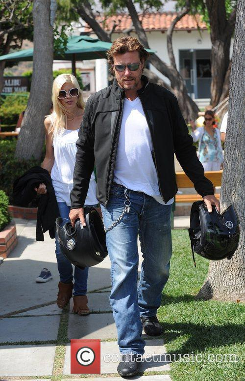 Tori Spelling and Dean McDermott carrying motorcycle helmets...