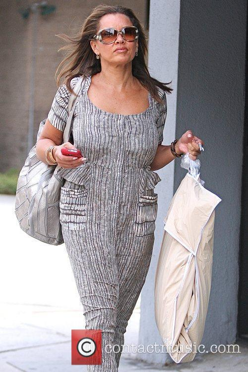 Vanessa Williams carrying a garment bag while running...