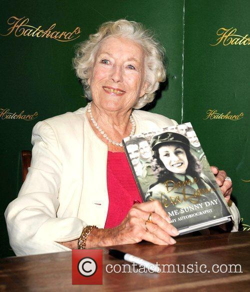 Signs copies of her autobiography 'Some Sunny Day'...