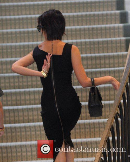 Victoria Beckham, wearing a black zib back dress,...