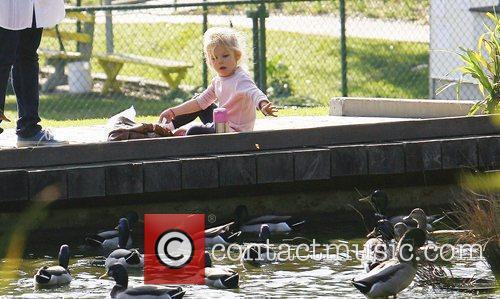 Violet Affleck feeding the ducks on a park...