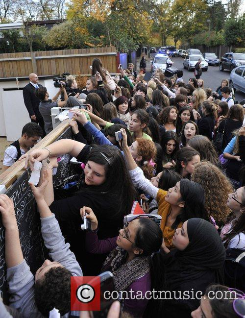 Are greeted by fans outside the X Factor...
