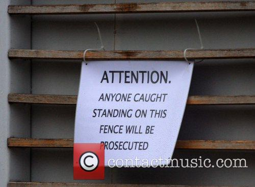 A sign posted on the fence of the...