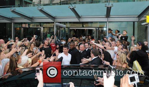 Is surrounded by fans as the 'X Factor'...
