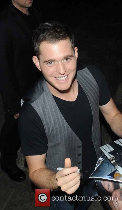 Michael Buble signs autoraphs for fans as he...