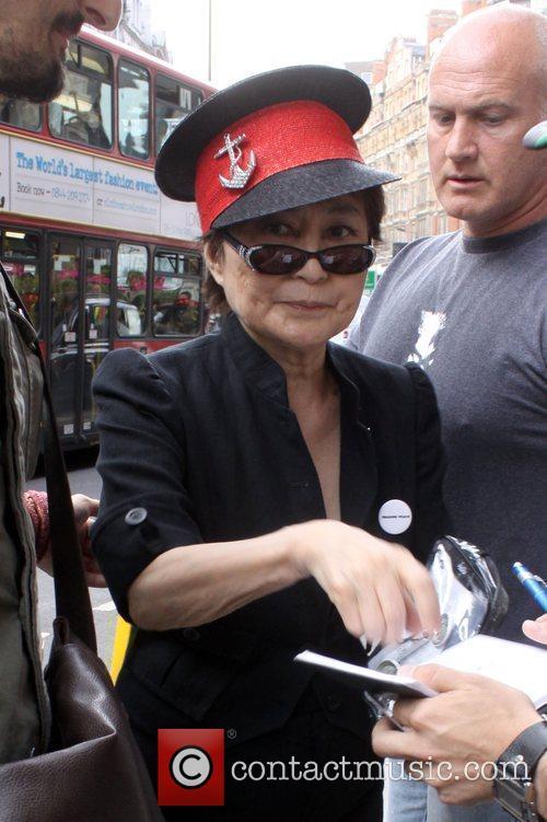 Signs an autograph
