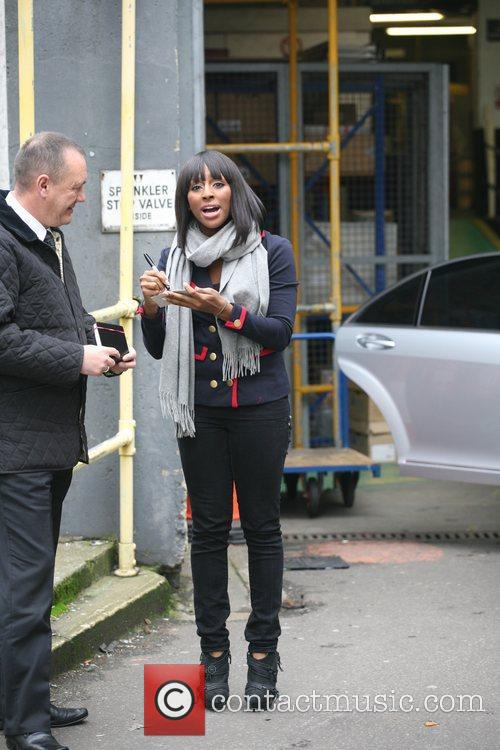 Alexandra Burke signs an autograph as she leaves...