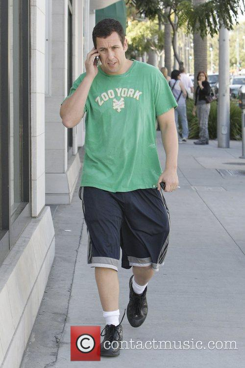 Adam Sandler talks on his mobile phone whilst...