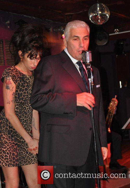 Amy Winehouse sheepishly standing behind her father Mitch...