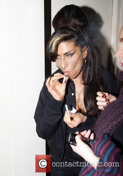 Amy Winehouse lights up a cigarette as she...