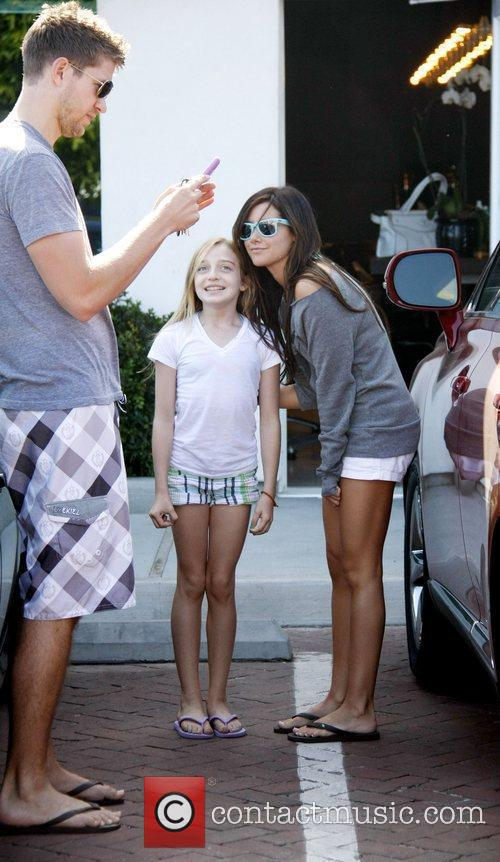 Ashley Tisdale poses with a young fan while...