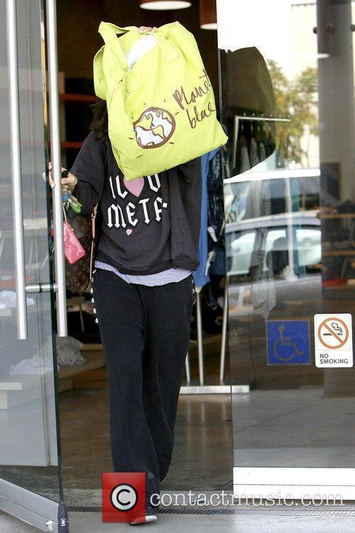 Covers her face with her shopping bag as...