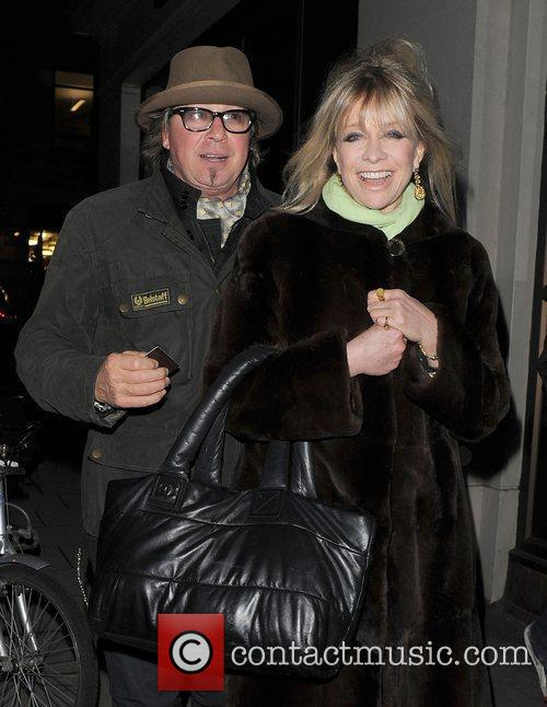 Jo Wood walks arm in arm with a...